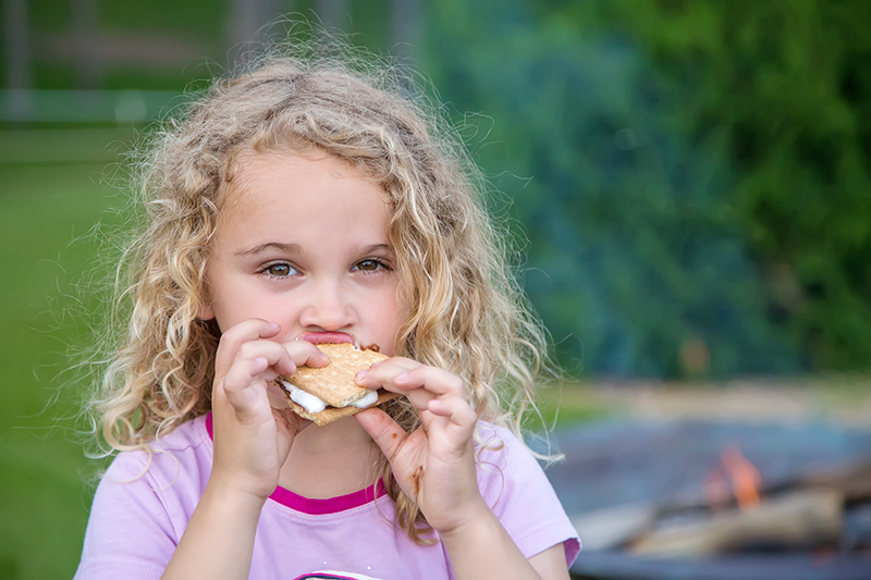 Girl eating Smores on the patio