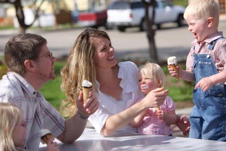 Family having ice cream cones together at park